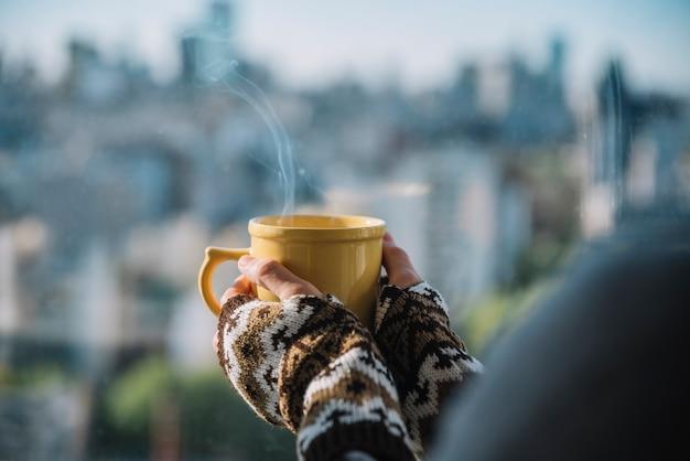 Manos con taza de bebida caliente.