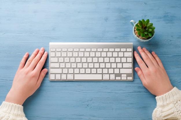 Manos con un teclado sobre la mesa. la chica trabaja en la computadora.