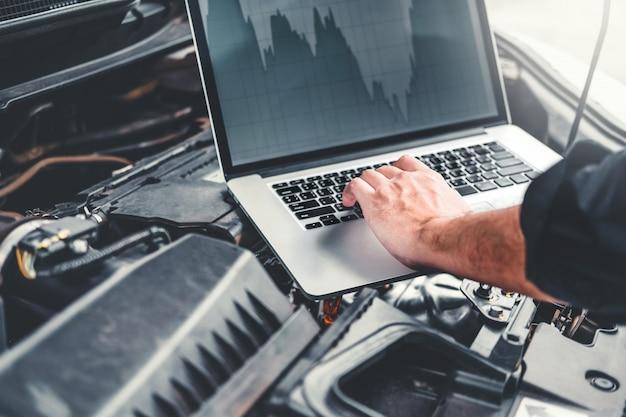 Manos de técnico profesional para verificar el servicio de reparación de motores de automóviles utilizando una computadora portátil