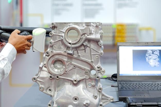 Las manos del técnico usan el escaneo 3d para escanear una parte del auto que se muestra en la vieja pantalla del portátil