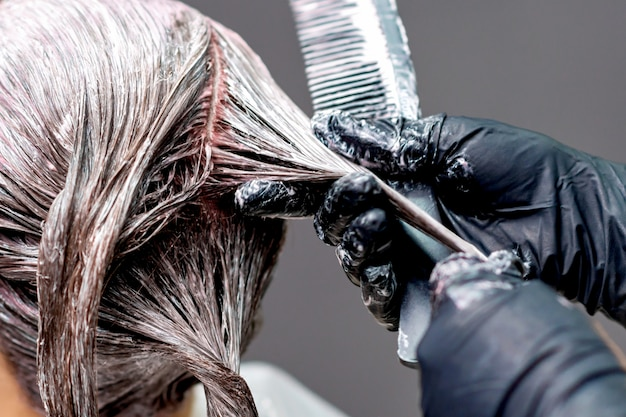 Manos teñiendo el cabello de la mujer.
