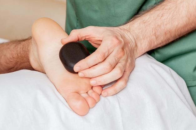 Manos del terapeuta de masaje dando masaje a los pies de la mujer por piedras calientes en el spa.