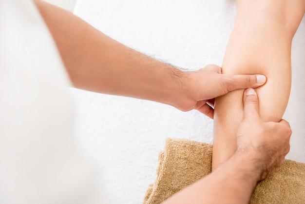 Manos del terapeuta masculino dando masaje a una pierna de mujer
