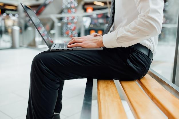 Manos del tipo de hombre de negocios en el teclado de la computadora, primer plano, vista de perfil