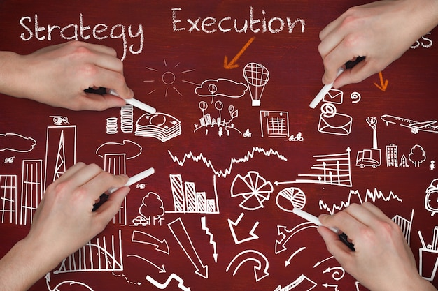Manos con tizas planeando la estrategia de negocio