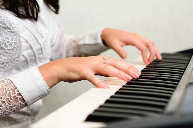 Manos tocan composición musical en piano