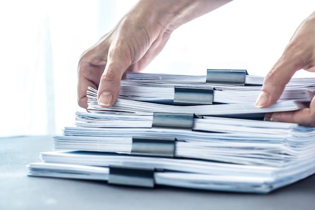 Manos tocando el papel de oficina. apila archivos de documentos con un clip negro.