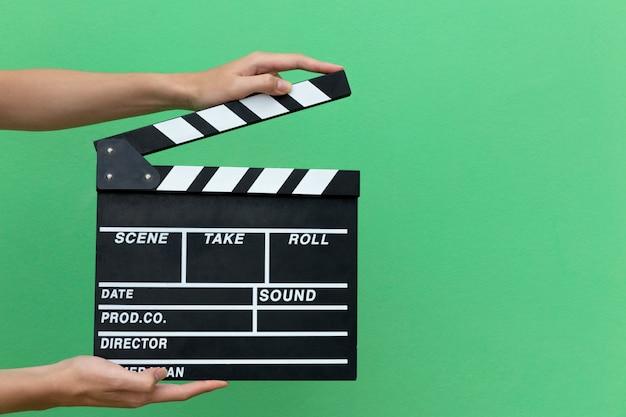 Las manos toman acción de película de equipo de pizarra de claqueta para gritar la película.