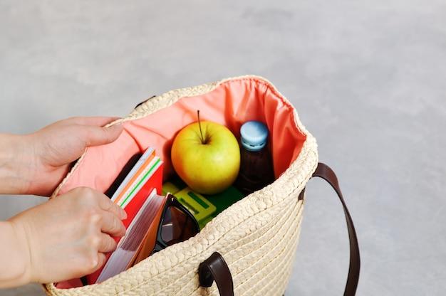 Las manos toman la elegante bolsa de mimbre de moda con libros de texto y cuadernos