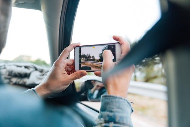 Manos tomando fotos en el teléfono en viaje