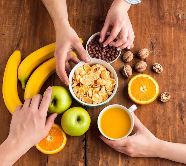 Manos tomando saludable desayuno casero de muesli, manzanas, frutas frescas y nueces
