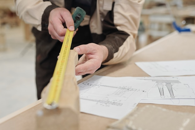 Manos de trabajador contemporáneo de fábrica sosteniendo una pieza de madera y midiendo su longitud por lugar de trabajo con bocetos de este detalle