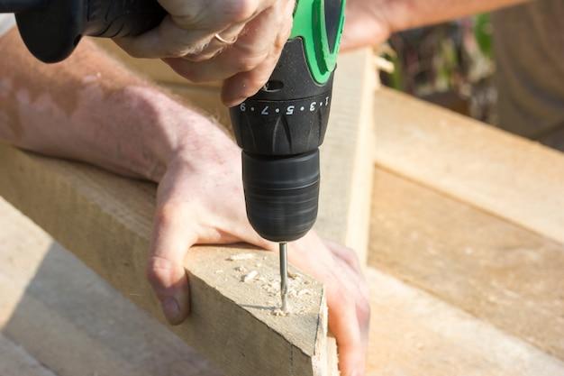 Las manos trabajadoras de un carpintero apretando un destornillador eléctrico se atornillan en madera