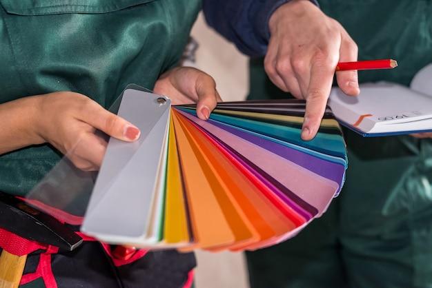 Manos de los trabajadores eligiendo el color para pintar en el muestreador