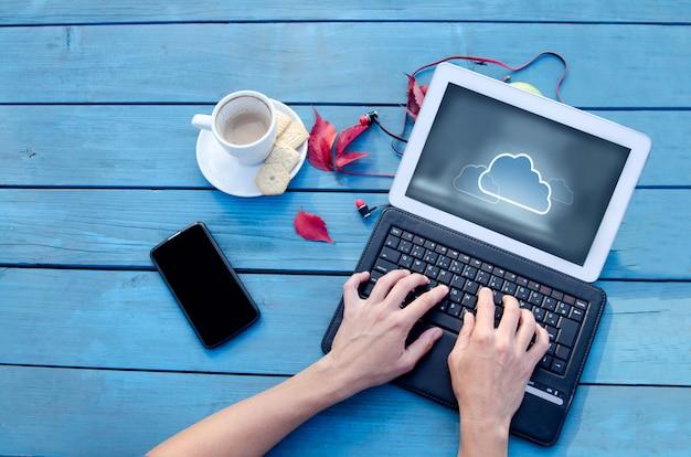 Manos trabajando en computadora portátil con tecnología de nube en pantalla