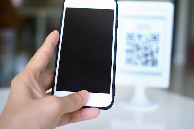 Las manos usan el teléfono para escanear códigos qr para recibir descuentos en las compras.