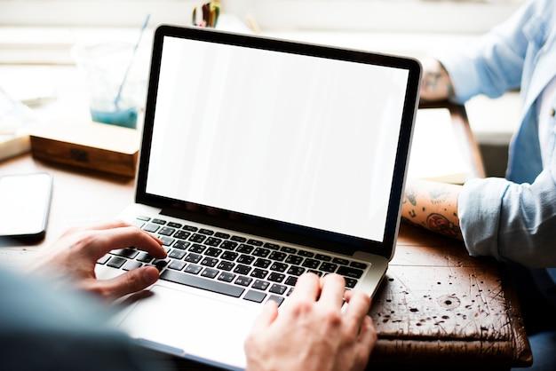 Manos usando la computadora portátil con pantalla en blanco