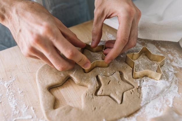 Manos usando cortador de galletas en pastelería