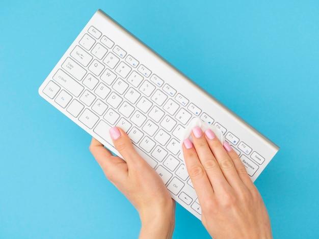 Manos usando una servilleta para limpiar el teclado