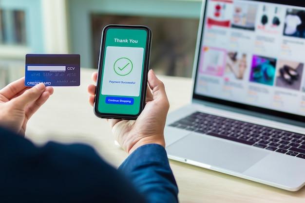Manos usando un teléfono y tarjeta de crédito para pago en línea