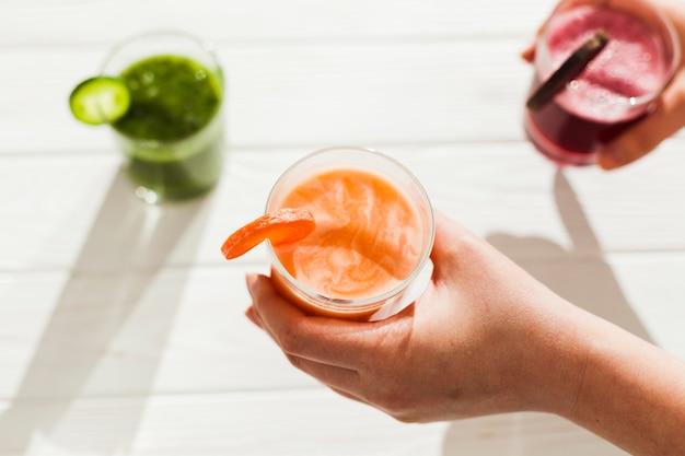 Manos con vasos de bebida colorida