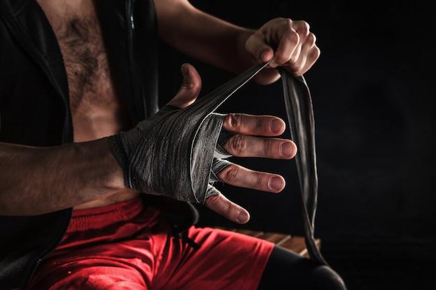 Las manos con vendaje de kickboxing de entrenamiento de hombre musculoso en negro