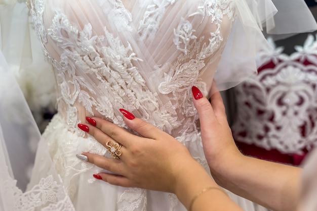 Manos de vendedores con vestido de novia, cerrar