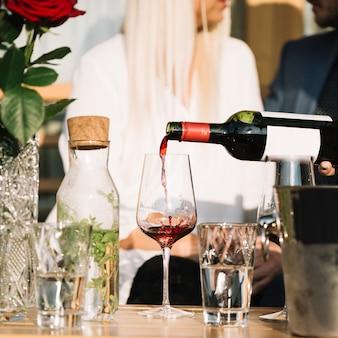Manos vertiendo vino en vaso de botella con pareja en segundo plano