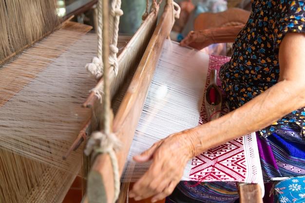Las manos de la vieja mujer tejiendo, el antiguo método de tejer.