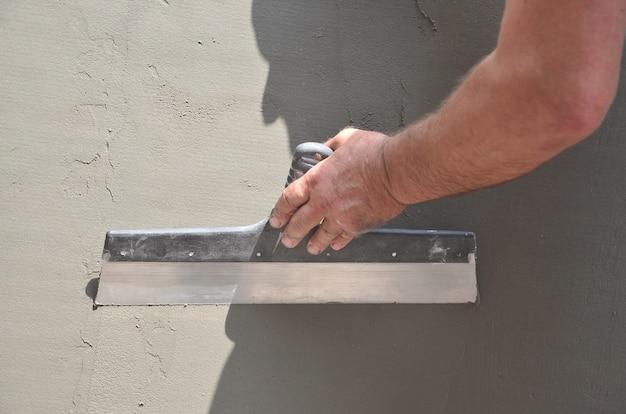 Manos de un viejo trabajador manual con herramientas de enlucido de paredes para renovar la casa