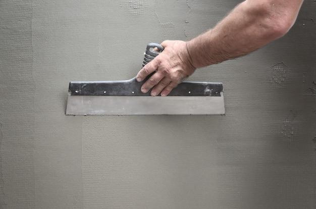 Manos de un viejo trabajador manual con la pared que enyesa las herramientas que renuevan la casa.