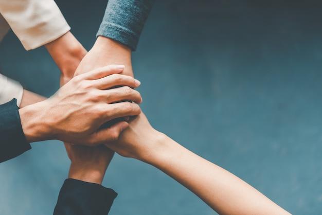 Las manos de la vista superior de la gente de negocios se juntan en una pila de manos para simbolizar la colaboración, el trabajo en equipo para alcanzar las metas y el éxito.