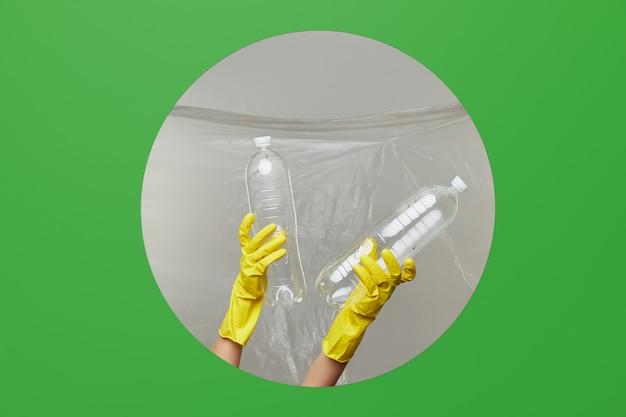 Las manos voluntarias en guantes amarillos sostienen botellas de plástico para reciclar a través del orificio redondo en fondo verde