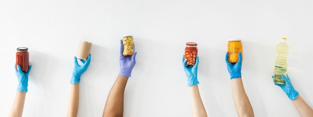 Manos del voluntario con guantes sosteniendo provisiones para donación