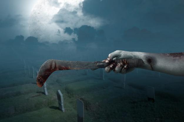Manos de zombie con herida sosteniendo hoz con el fondo de la escena nocturna