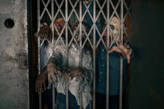 Manos de zombie que sobresalen del ascensor, horror