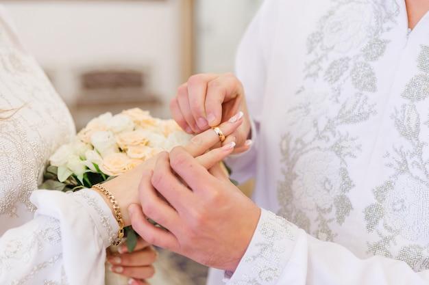 Mans mano poniendo un anillo de bodas en el dedo de una mujer