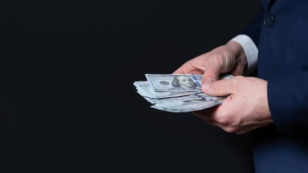 Mans manos con dólares en un primer plano de fondo negro