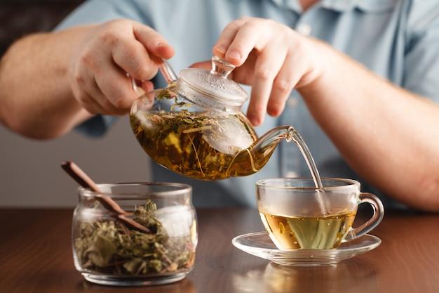 Mans manos y vaso de té de hierbas medicinales