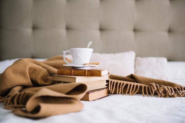 Manta cerca de libros y taza blanca