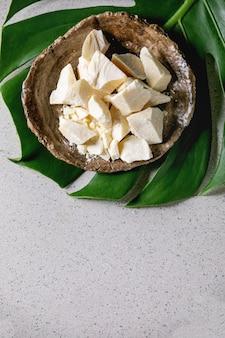 Manteca de cacao picada en un tazón y hoja de monstera