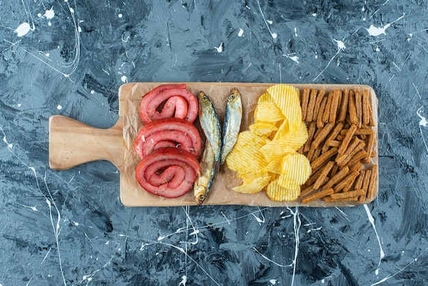 Manteca de cerdo, pescado, patatas fritas y pan rallado sobre tabla de cortar en azul.