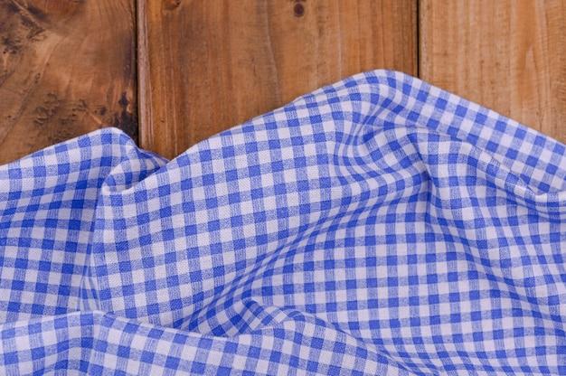 Mantel de cocina a cuadros azul sobre mesa de madera rústica