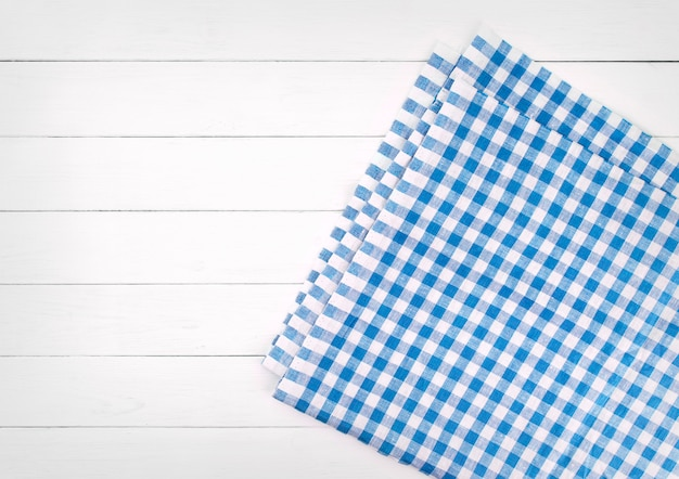 Mantel a cuadros azul sobre mesa de madera blanca