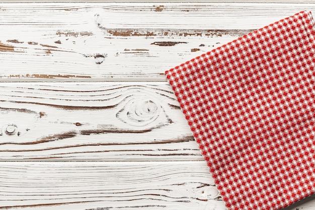 Mantel a cuadros rojo sobre mesa de madera