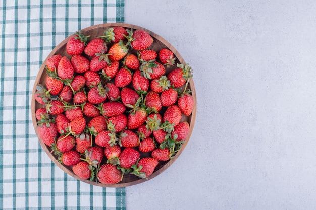 Mantel debajo de un gran cuenco lleno de fresas sobre fondo de mármol. foto de alta calidad