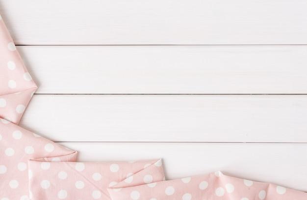 Mantel de lunares rosa claro doblado sobre mesa de madera blanqueada.