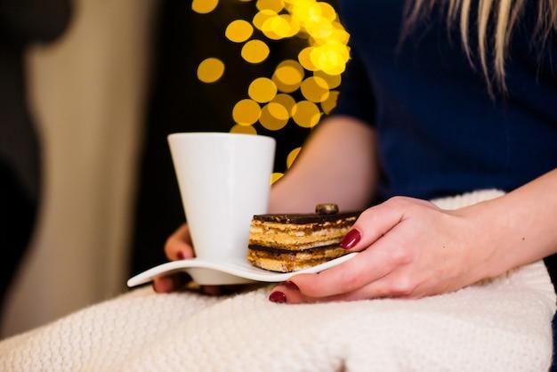 Mantén las manos una taza de café y un pastel.