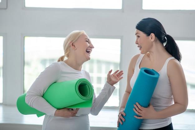 Mantener la forma. mujer rubia y mujer morena con alfombras de yoga y riendo
