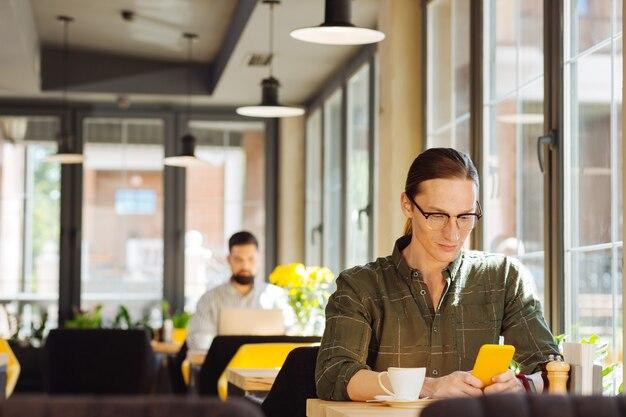 Mantenerse conectado. hombre guapo serio mirando la pantalla del teléfono inteligente mientras recibe un mensaje de su amigo